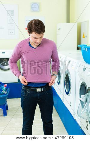 Young man in a launderette, washing his dirty laundry, in the background are washing machines, he is angry about his undersized top