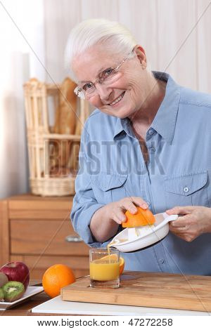 Elderly woman pouring freshly squeezed orange juice