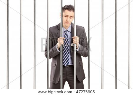 Handcuffed businessman in suit posing in jail and holding bars, isolated on white background