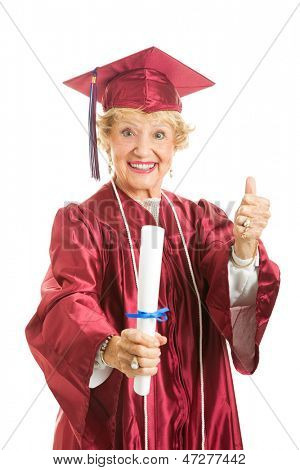 Happy senior lady graduates in her cap and gown, giving thumbs up.