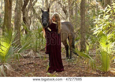 medieval woman in dress with horse in forest
