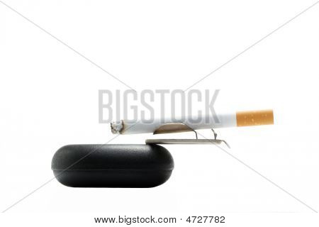 Cigarette On Ashtray Over White