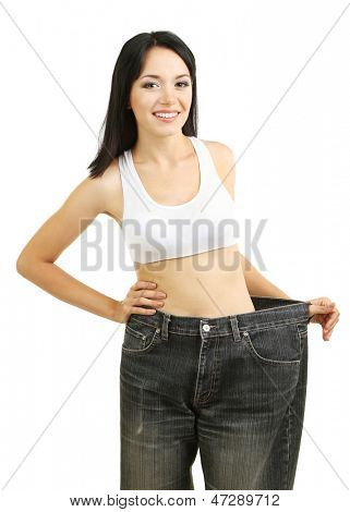 Beautiful young woman with big jeans isolated on white