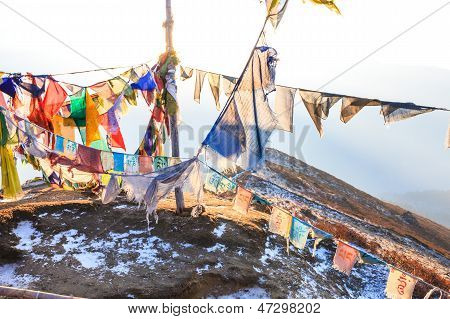 Praying flags floating in the wind in front of the Kangchenjunga is the third highest mountain