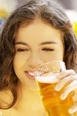 Attractive young woman drinking beer on sidewalk cafe.