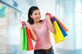 stock photo of department store  - Happy Asian shopping woman smiling holding many shopping bags at the mall - JPG
