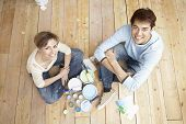 High angle portrait of happy couple with painting tools sitting on wooden floor