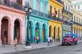 HAVANA-JUNE 21:Typical street scene with people and colorful buildings on June 21, 2013 in Havana.Wi