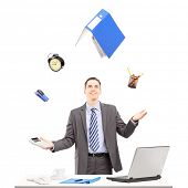 Young businessman in a suit juggling with office supplies in his office, isolated on white backgroun