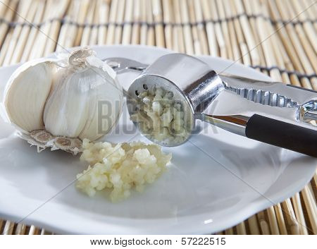 Fresh Garlic Crushed By Garlic Crusher On White Dish On Kitchen Table Top Use For Food  Spice And In