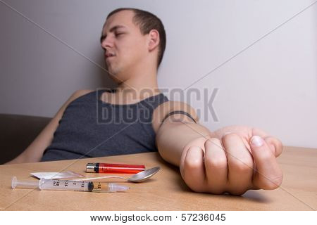 Heroin, Syringe, Spoon, Lighter On The Table And Stoned Male Addict