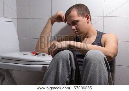 Depressed Man With Heroin Addiction Sitting In Bathroom