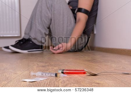 Syringe With Drugs And Addict Sitting On The Floor