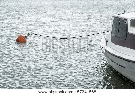 White Boat In Harbour With Red Buoy And Rope