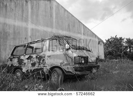 old and rusted car in black and white