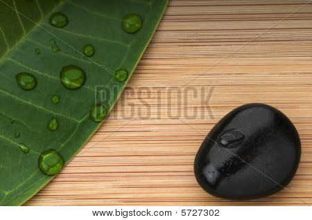 Green Leaf And Black Stone With Rain Droplets On The Bamboo Background