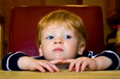 stock photo of fidget  - Cute little boy patiently wating at the kitchen table - JPG
