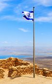 foto of masada  - Israel flag over fortress Masada in Israel - JPG