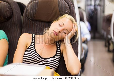 Lady traveling napping on a train.