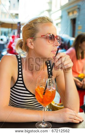 Woman with cocktail in street cafe.