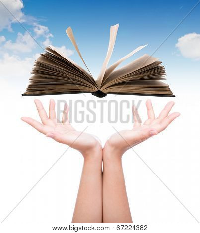 Women hand holding book over blue sky