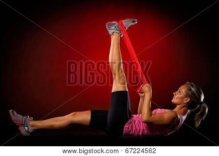 young woman exercise with elastic fitness band in the gym