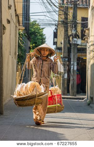 HOI AN, VIETNAM - MARCH 31: Unidentified old woman in traditional Vietnamese clothes carrying buskets with bread on the street in Hoi An, Vietnam on March 31, 2014.