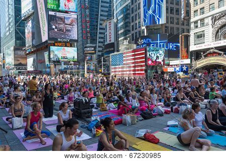 Thousands of New Yorkers are make the first day of summer by practicing yoga in Times Square