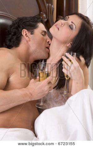 Amar o jovem casal Sensual com champanhe na cama