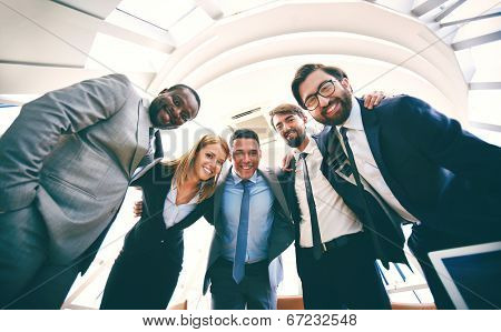 Group of successful business people in suits looking at camera