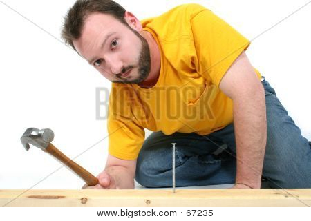 Man Hammering In Nail