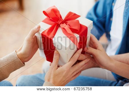 Close-up of female hands taking giftbox