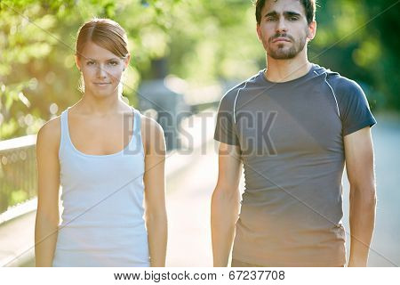 Photo of young sporty couple in activewear outdoors