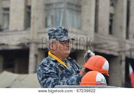 KIEV, UKRAINE - APR 19, 2014: Artist painting working helmets for tourists in the rioters camp. Putsch of Junta in Kiev. Kiev.April 19, 2014 Kiev, Ukraine