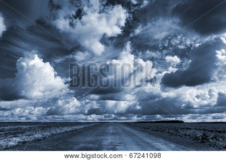 Empty Asphalt Country Road Under Dark Dramatic Cloudy Sky