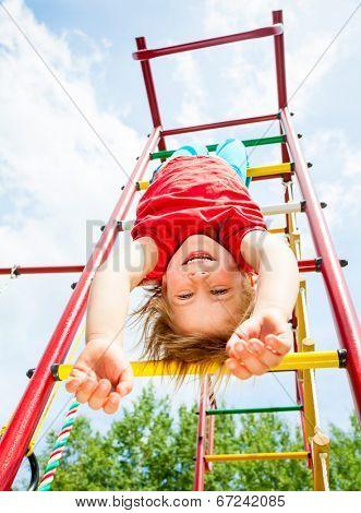 Little girl having fun playing on monkey bars