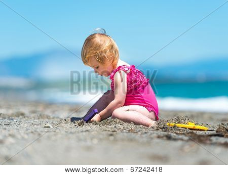 cute baby girl playing in the sand with a shovel on the beach on a summer day