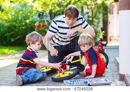 Father And Two Little Sons Reparing Bikes Together