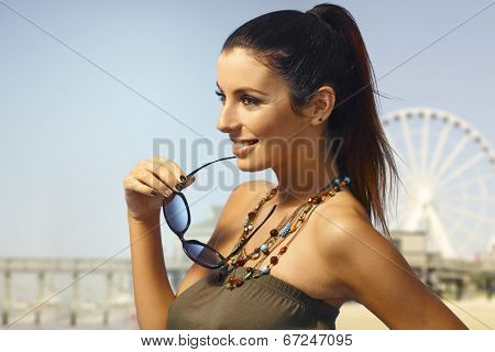 Summer portrait of attractive young woman outdoors, smiling happy.