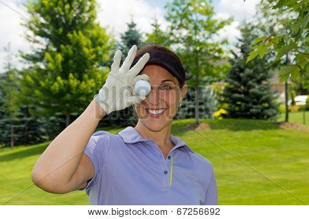 Female Golfer Holding A Golf Ball Over Her Eye