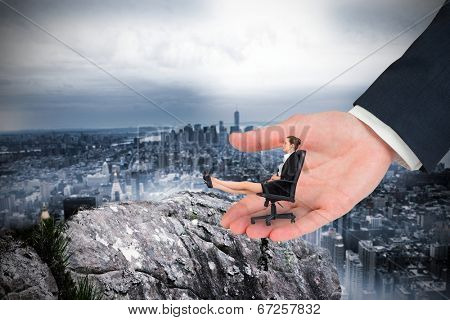 Businesswoman sitting on swivel chair with feet up in large hand against large rock overlooking huge city