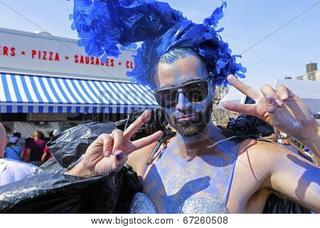 Young man in blue makeup salutes the camera
