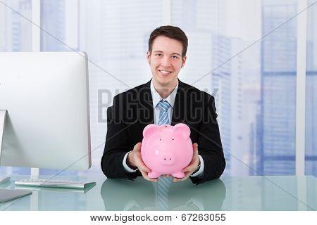 Businessman Holding Piggybank At Desk