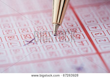 Pen Marking Numbers On Lottery Ticket