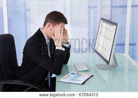 Businessman Suffering From Headache At Computer Desk