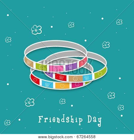 Colorful bangles on floral decorated green background for Happy Friendship Day celebrations.