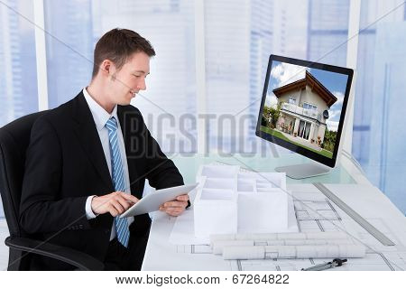 Architect Browsing Property On Computer In Office
