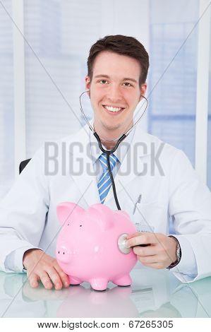 Doctor Examining Piggybank With Stethoscope In Hospital
