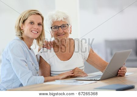 Homecarer with elderly woman using laptop computer