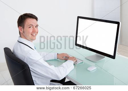 Confident Male Doctor Working On Computer At Desk